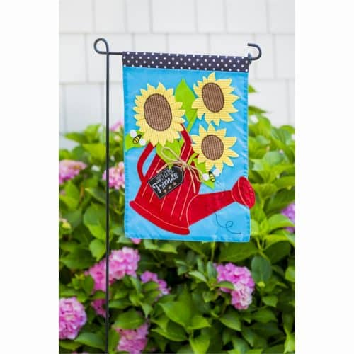 garden stand with sunflower flag handing with flowers in the back